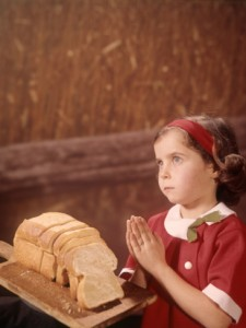 h-armstrong-roberts-young-girl-saying-prayer-praying-loaf-bread-wheat-field-background