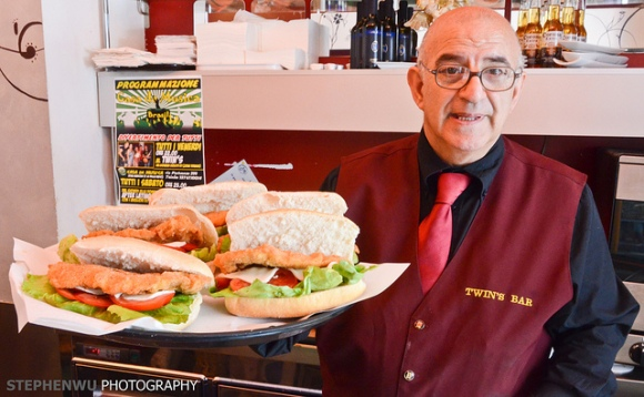 Italian waiter carrying tray of subs