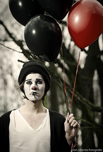 sad mime holding onto balloons