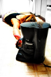 tired girl on kitchen floor with coffee maker
