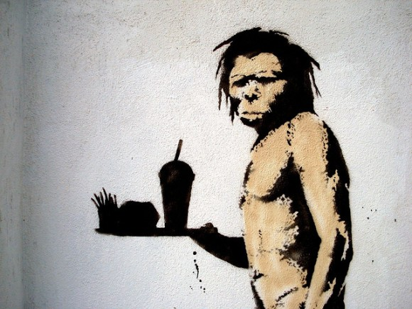 Banksy caveman with burger and soda